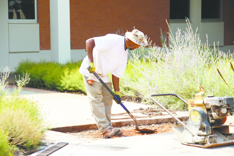Construction worker Darrell Dixon shovels gravel to repair the sidewalk. Photo by Farhin Lilywala.